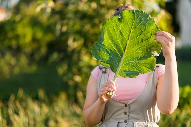 Vooraanzicht meisje met sla blad Gratis Foto