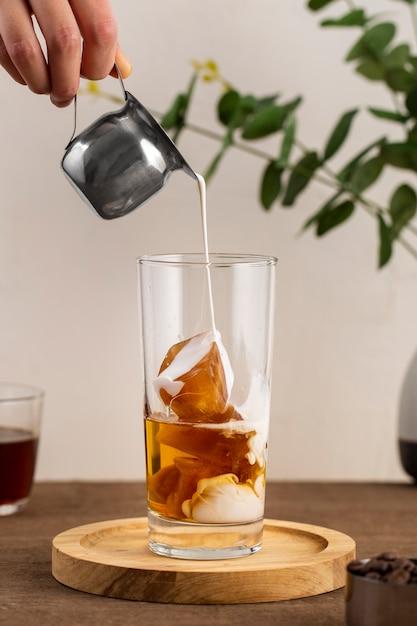 Vooraanzicht melk gieten over ijskoffie Gratis Foto