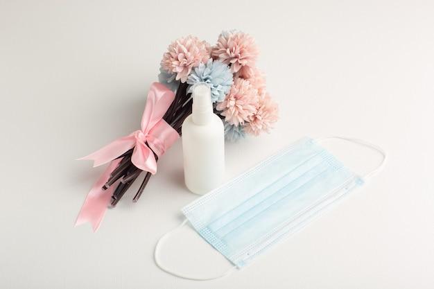 Vooraanzicht mooie bloemen met spray en masker op wit oppervlak Gratis Foto