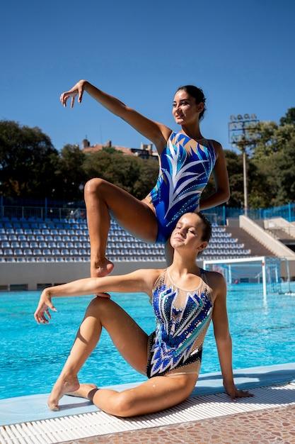 Vooraanzicht mooie meisjes poseren bij het zwembad Gratis Foto