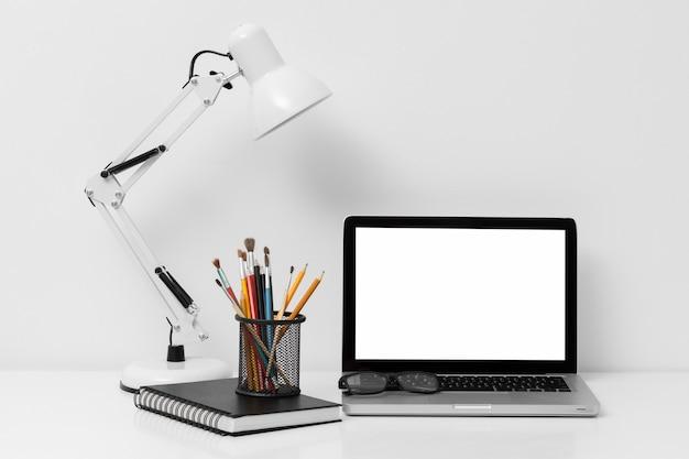 Vooraanzicht opstelling van kantoorelementen met laptop Gratis Foto