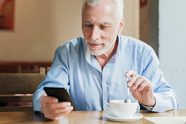 Vooraanzicht oude man kijkend naar zijn telefoon Gratis Foto