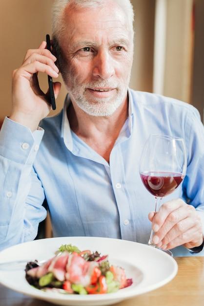 Vooraanzicht oude man praten over zijn telefoon Gratis Foto