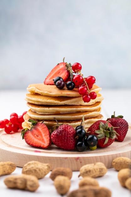 Vooraanzicht pannenkoeken met aardbeien zwarte en rode aalbessen op een dienblad met pinda's Gratis Foto