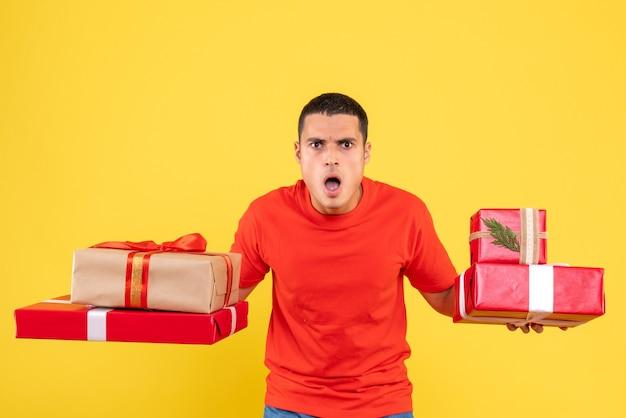 Vooraanzicht presenteert jonge mannelijke kerstcadeautjes verrast op gele achtergrond Gratis Foto