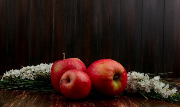 Vooraanzicht rode appels met witte bloemen op een houten achtergrond Gratis Foto