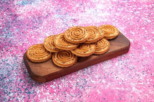 Vooraanzicht ronde zoete koekjes bekleed op de roze achtergrond. Gratis Foto
