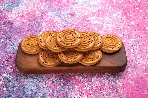 Vooraanzicht ronde zoete koekjes bekleed op roze bureau. Gratis Foto