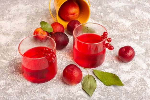 Vooraanzicht rood pruimensap met verse pruimen op heldere vruchtensapdrank Gratis Foto