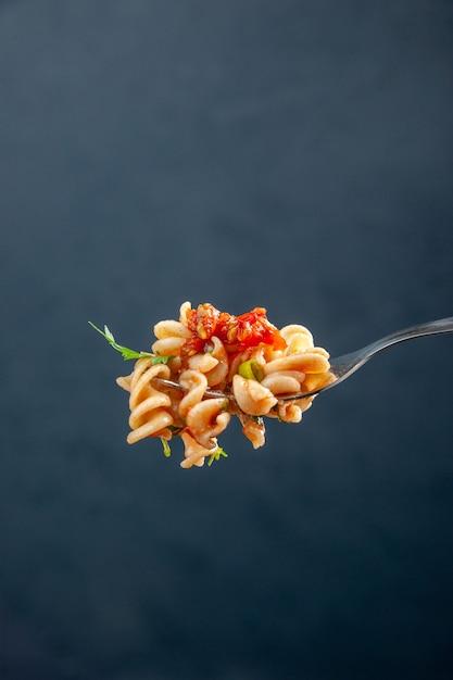 Vooraanzicht rotini pasta op vork op donkere geïsoleerde oppervlakte vrije ruimte Gratis Foto