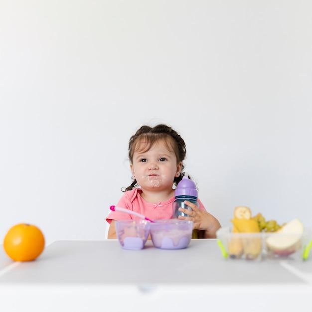Vooraanzicht schattig jong meisje aan het ontbijt Gratis Foto