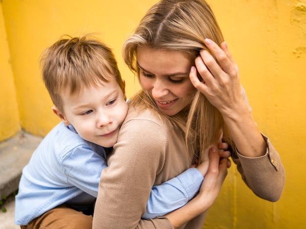 Vooraanzicht schattige zoon knuffelen zijn moeder Gratis Foto