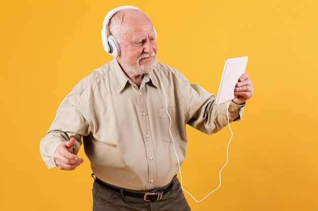 Vooraanzicht senior luisteren muziek op tablet Gratis Foto