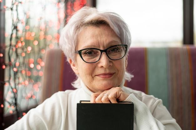 Vooraanzicht senior vrouw met glazen boek houden Gratis Foto