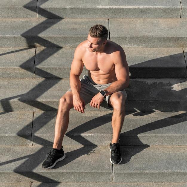 Vooraanzicht shirtless atletische man zittend op trappen Gratis Foto