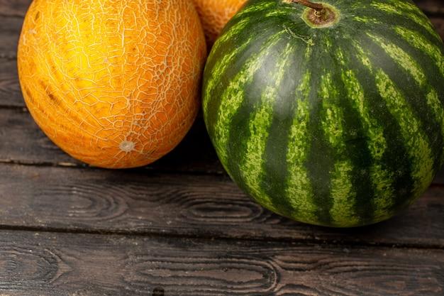 Vooraanzicht sluiten groene watermeloen en meloenen op de bruine Gratis Foto