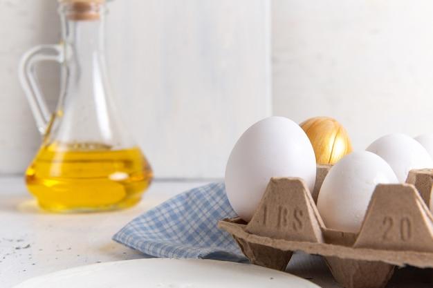 Vooraanzicht sluiten witte hele eieren met gouden op de witte muur Gratis Foto