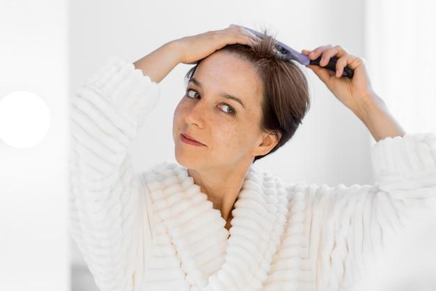 Vooraanzicht smiley vrouw haar haren borstelen Gratis Foto