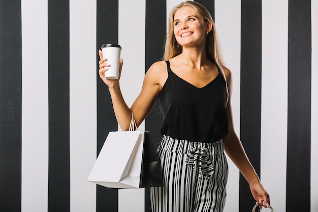 Vooraanzicht smiley vrouw met boodschappentassen Gratis Foto