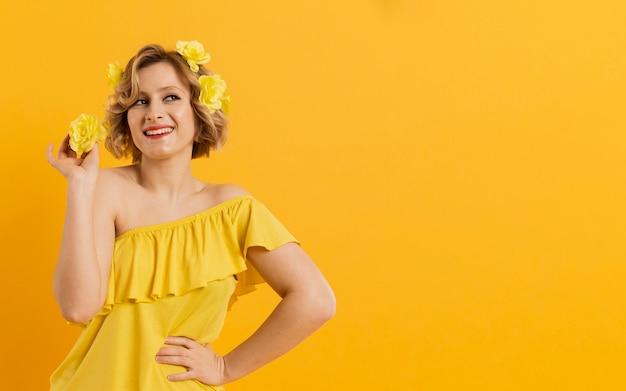 Vooraanzicht smiley vrouw met gele bloemen Gratis Foto