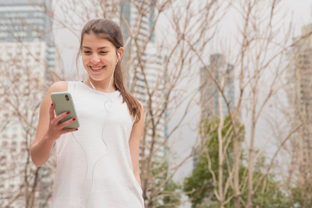 Vooraanzicht smiley vrouw met haar telefoon Gratis Foto