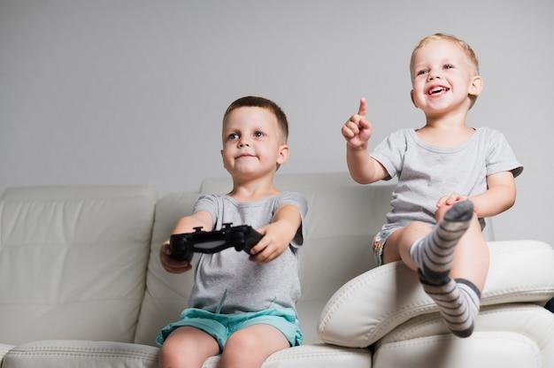 Vooraanzicht smileyjongens spelen met controllers Gratis Foto