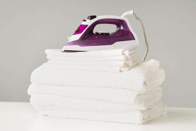 Vooraanzicht stapel handdoeken met ijzer Gratis Foto