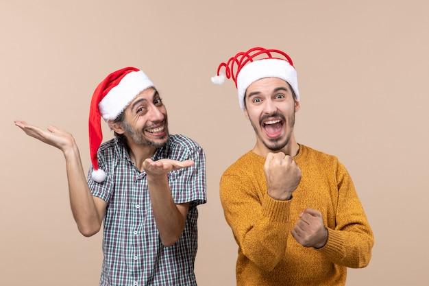 Vooraanzicht twee gelukkige jongens met kerstmutsen waarvan één met open handen en de andere stoten op beige geïsoleerde achtergrond Gratis Foto