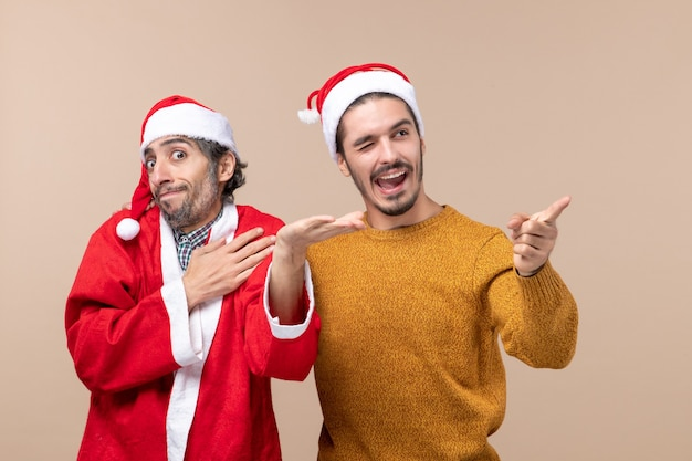 Vooraanzicht twee xmasmannen met santahoeden die zich op beige geïsoleerde achtergrond bevinden Gratis Foto