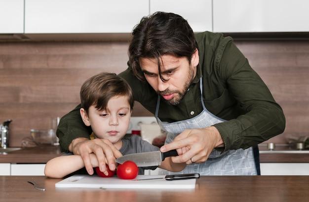 Vooraanzicht vader en zoon in keuken Gratis Foto
