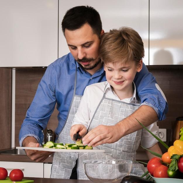 Vooraanzicht vader zoon onderwijzen om groenten te snijden Gratis Foto