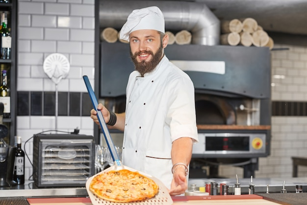 Vooraanzicht van bakker die de uniformjas van de chef-kok draagt en pizza op metaalschop houdt. Premium Foto