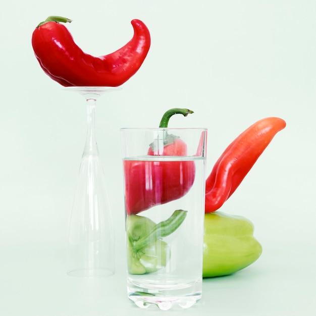 Vooraanzicht van bell en chilipepers met een glas water Gratis Foto