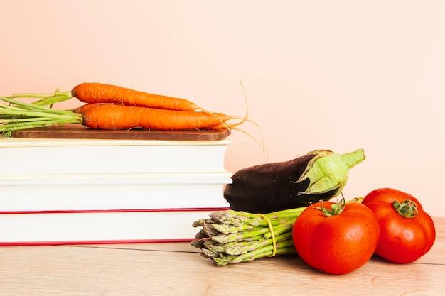 Vooraanzicht van boeken en groenten met effen achtergrond Gratis Foto