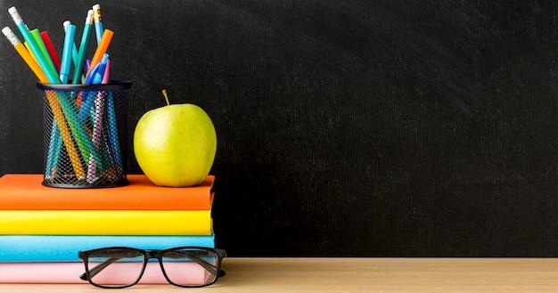 Vooraanzicht van boeken voor terug naar school met bril en kopie ruimte Premium Foto