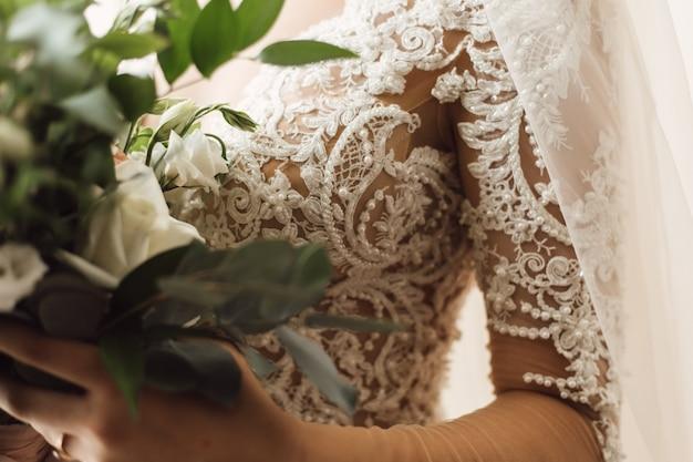 Vooraanzicht van borduurwerk op het korset van trouwjurk en bruiloft boeket van witte eustomas Gratis Foto
