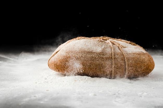Vooraanzicht van brood en bloem op zwarte achtergrond Gratis Foto