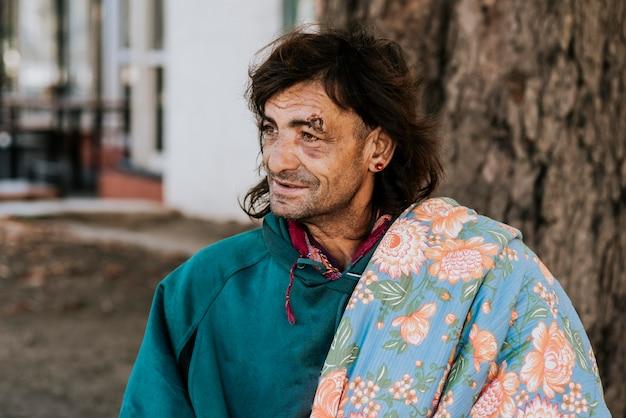 Vooraanzicht van dakloze man met deken op schouder Gratis Foto