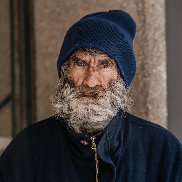 Vooraanzicht van dakloze man met een baard buitenshuis Gratis Foto