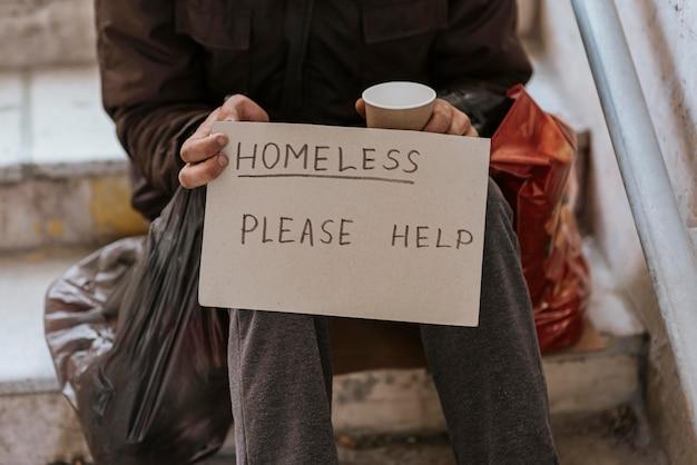 Vooraanzicht van dakloze man met hulpteken en plastic zak Gratis Foto