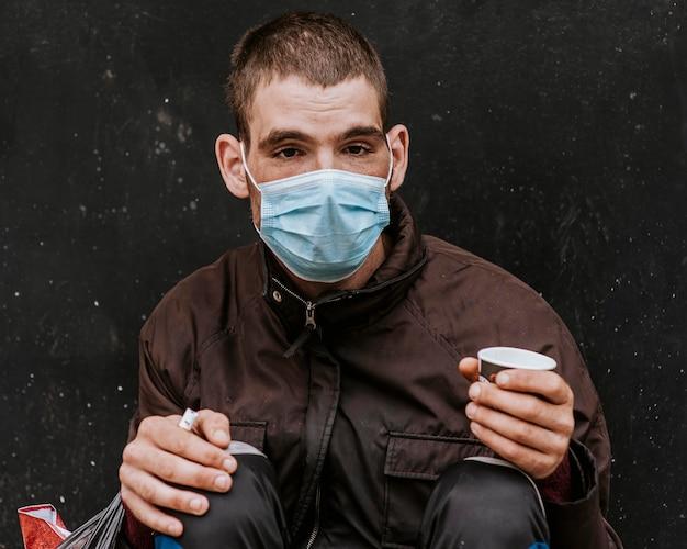 Vooraanzicht van dakloze man met medisch masker buitenshuis en beker Premium Foto