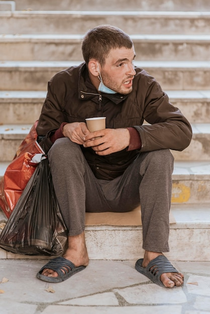Vooraanzicht van dakloze man op trappen met beker en plastic zak Gratis Foto