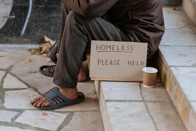 Vooraanzicht van dakloze man op trappen met helpteken en beker Gratis Foto