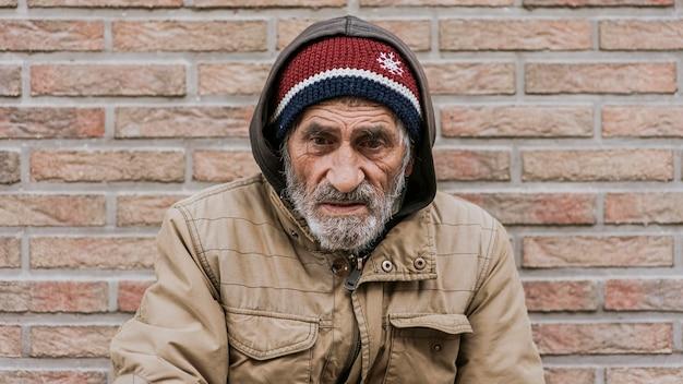 Vooraanzicht van dakloze man voor muur Gratis Foto