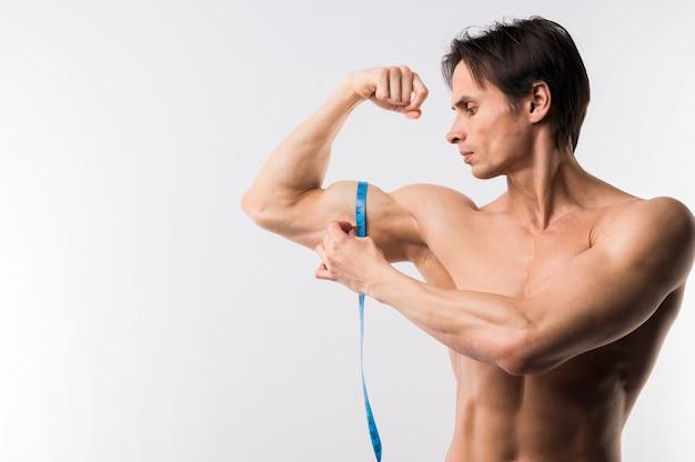 Vooraanzicht van de atletische man meten biceps Gratis Foto