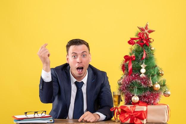 Vooraanzicht van de gelukkige man die geld verdient teken zittend aan de tafel in de buurt van kerstboom en presenteert op geel Gratis Foto