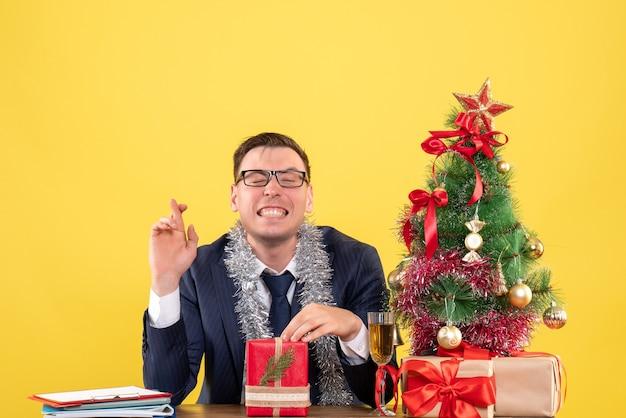 Vooraanzicht van de gelukkige man die geluk teken zittend aan de tafel in de buurt van de kerstboom en cadeautjes op geel Gratis Foto