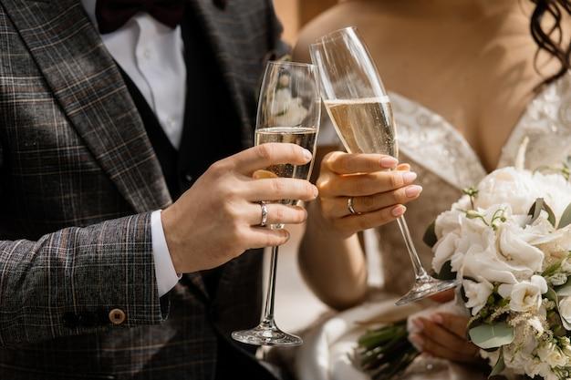 Vooraanzicht van de handen van het bruidspaar met champagneglazen en huwelijksboeket Gratis Foto