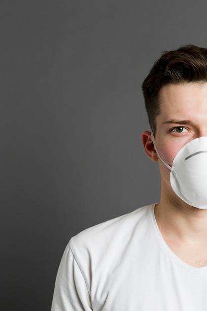 Vooraanzicht van de helft van iemands gezicht dat een medisch masker draagt Gratis Foto