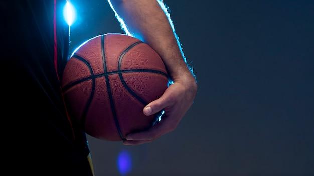 Vooraanzicht van de holdingsbal van de basketbalspeler met exemplaarruimte Gratis Foto